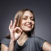 Portrait of happy smiling woman with okay gesture on dark grey background